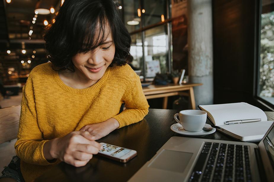 Femme qui pianotent sur son téléphone dans un café